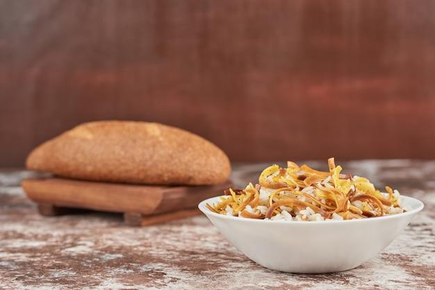 Bułeczki chlebowe z miską makaronu.