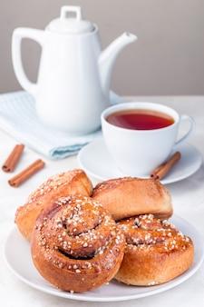 Bułeczki cynamonowe na białym talerzu, podawane z filiżanką czerwonej herbaty