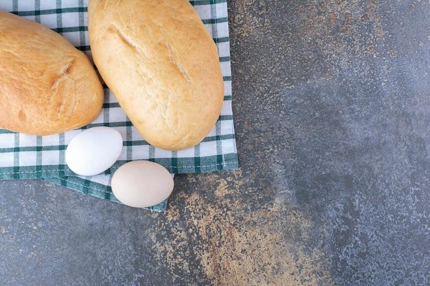 Bułeczki i jajka wystawione na ręczniku na marmurowej powierzchni
