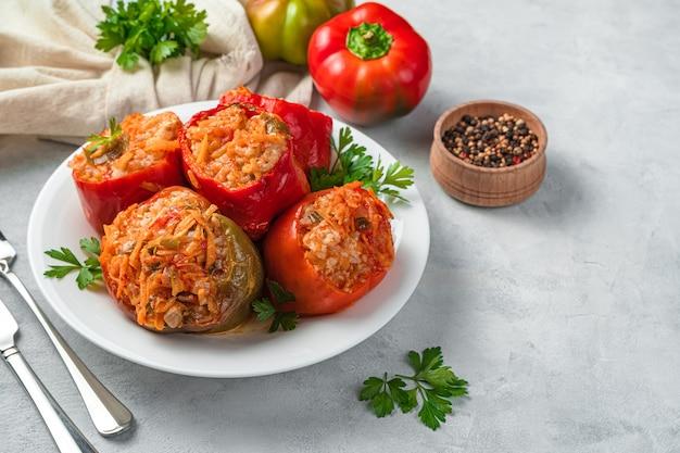 Bułgarska papryka faszerowana mięsem i ryżem z sosem na szarym tle ze świeżymi ziołami. widok z boku, miejsce na kopiowanie.