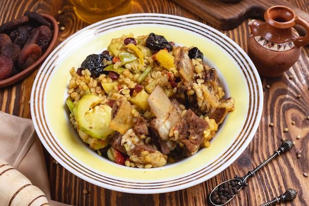 Bulgur z mięsem cukinia śliwki fasola papryka suchych owoców widok z boku