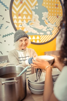 Bulion z kurczaka. miła starsza kobieta czeka na zupę będąc głodną