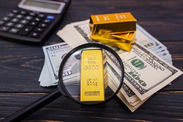 Bulion, złoto lub sztabka na banknocie dolara amerykańskiego z lupą i kalkulatorem