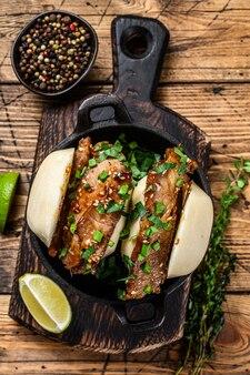 Bułka bao, kanapka gotowana na parze z wieprzowiną. drewniane tło. widok z góry.