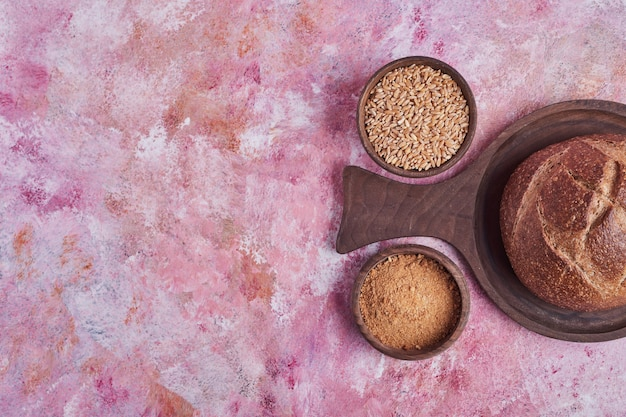 Bułka chlebowa i pszenna mieszanka na różowym stole.