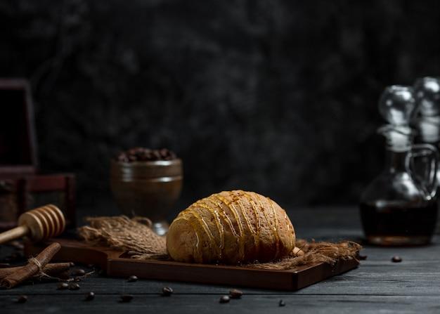 Bułka chlebowa z sosem karmelowym podana na rustykalnej desce