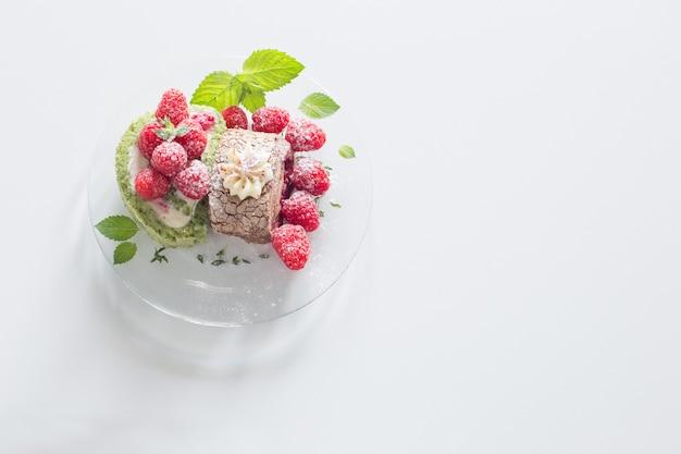 Bułka czekoladowa z malinami i listkami mięty na szklanym talerzu na białym stole