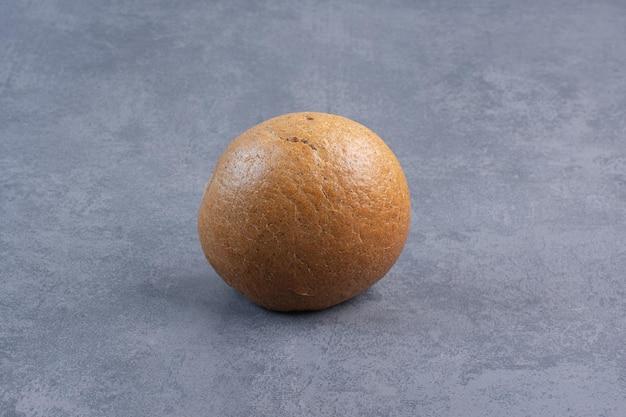 Bułka hamburgerowa stojąca pionowo na marmurowym tle. zdjęcie wysokiej jakości