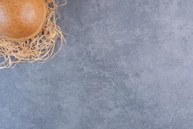 Bułka hamburgerowa zagnieżdżona w stos słomy na marmurowym tle. zdjęcie wysokiej jakości