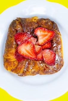 Bułka lub bułka z ciasta francuskiego. ciasto ze świeżymi truskawkami. pyszne pokusy słodyczy i deserów na żółtym tle.