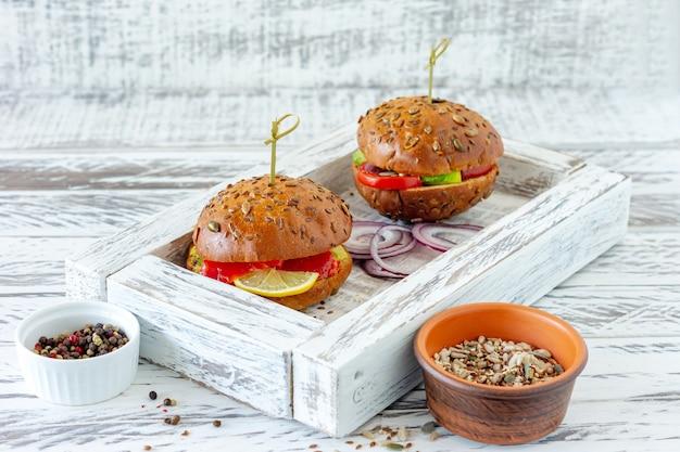 Bułka pełnoziarnista nadziewana sałatą, łososiem, awokado i pomidorami. koncepcja zdrowej żywności.