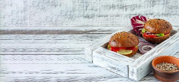 Bułka pełnoziarnista nadziewana sałatką, łososiem, awokado i pomidorami - świeżo upieczona bułka pełnoziarnista na śniadanie. transparent.