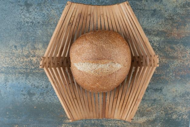 Bułka świeżego ciemnego chleba na drewnianym koszu