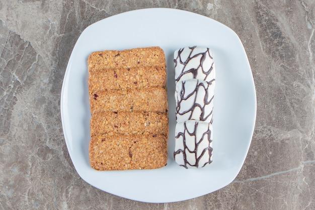 Bułka tarta i cukierki na talerzu na marmurze.