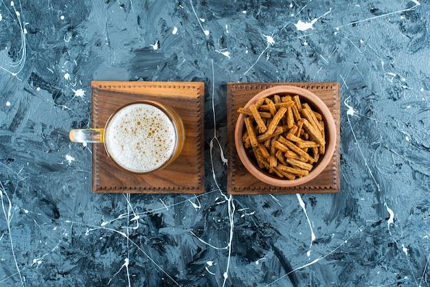 Bułka tarta i piwo na desce, na marmurowym stole.