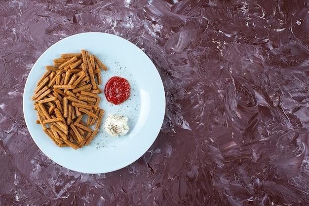 Bułka tarta z sosami na talerzu na marmurze.