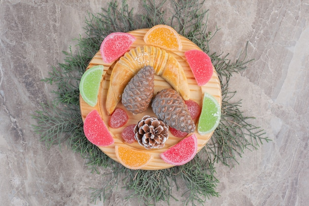 Bułka w kształcie półksiężyca na marmurze i szyszce ozdobiona półmiskiem na marmurze.