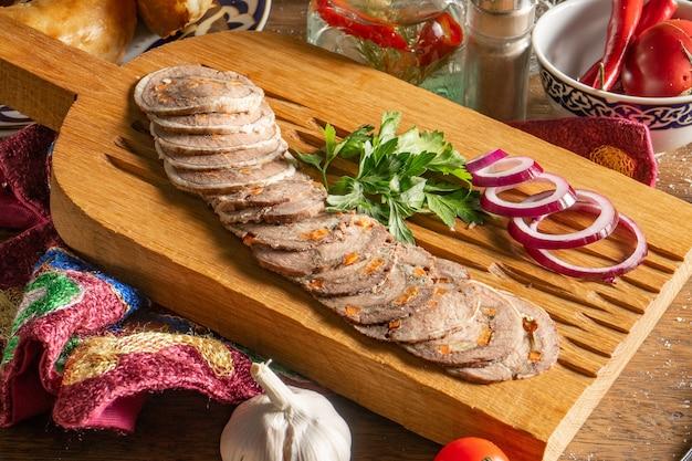 Bułka wołowa z serem suluguni, marchewką, ziołami, orzechami włoskimi, przyprawami, kolendrą i czerwoną cebulą, posiekana i podana na drewnianej desce do krojenia.