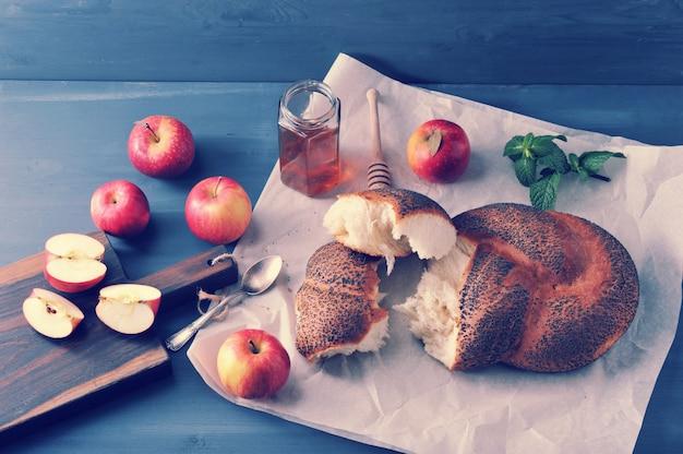 Bułka z makiem, rozdarta na kawałki zbliżenie jabłka, mięty i miodu
