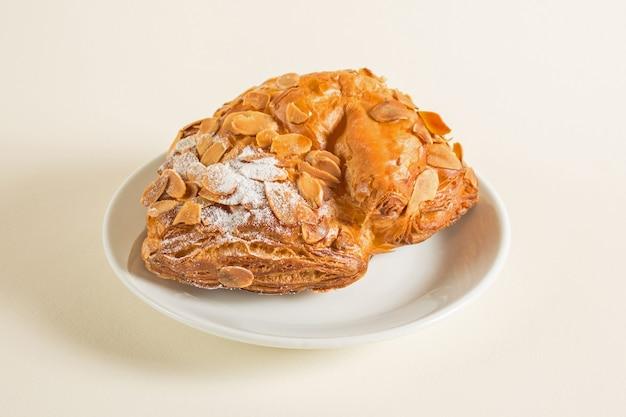 Bułka z nadzieniem czekoladowym i orzeszkami ziemnymi z ciasta francuskiego posypana cukrem pudrem.