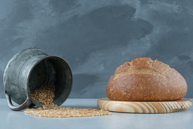 Bułka żytnia na drewnianej desce z kubkiem jęczmienia