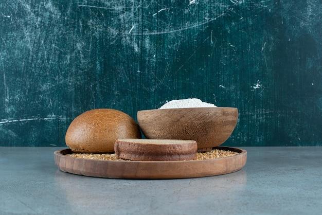 Bułka żytnia z miską mąki na drewnianym talerzu.