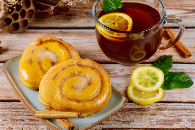 Bułki cynamonowe z polewą i filiżanką herbaty z cytryną i miętą