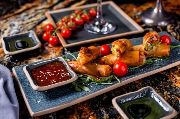 Bułki podawane z pomidorami, rukolą i sosem