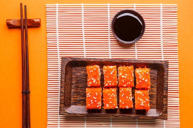 Bułki, sos sojowy, pałeczki na pomarańczowym stole, blat fotograficzny