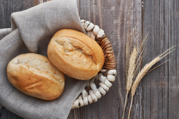 Bułki w koszyku na rustykalnym drewnie z kłosami pszenicy
