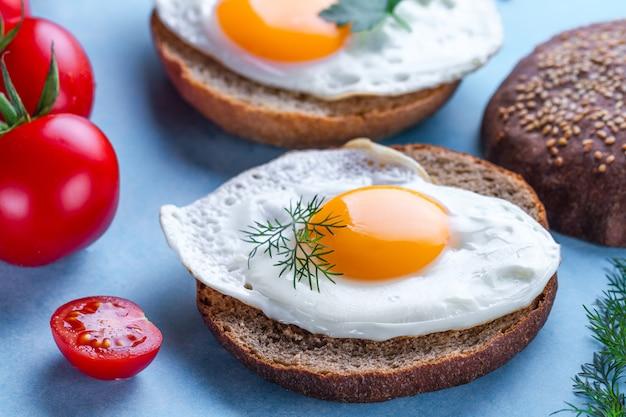 Bułki z domowymi, smażonymi jajkami drobiowymi na zdrowe śniadanie na niebieskiej powierzchni. żywność białkowa. kanapki jajka