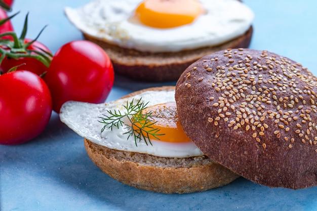 Bułki z domowymi, smażonymi jajkami drobiowymi posypane przyprawami i solą na śniadanie na niebieskim blacie. żywność białkowa. kanapki jajka