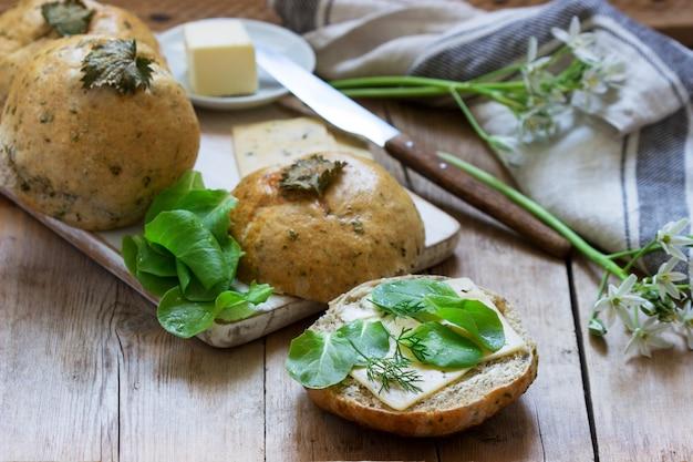 Bułki z pokrzywy podawane z masłem, serem i zieleniną. styl rustykalny.