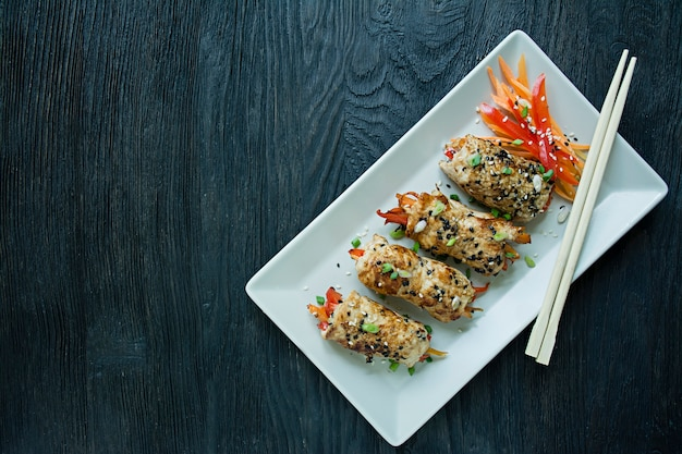 Bułki ze świeżą piersią kurczaka z zieleniną, plasterkami marchewki, papryką na ciemnej desce do krojenia.