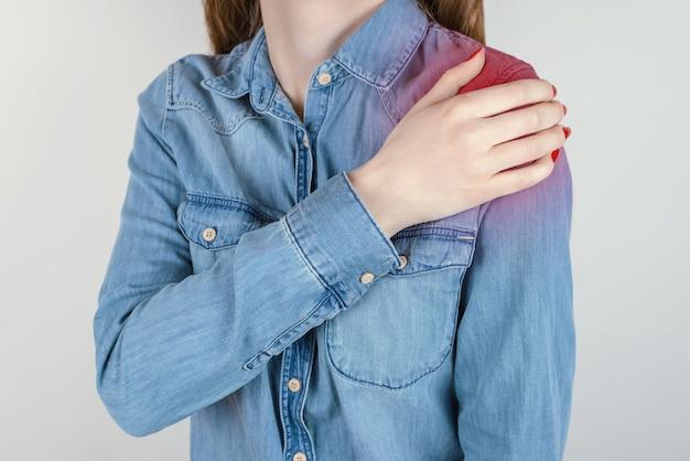 Bump chronicznej koncepcji fitness. przycięte zdjęcie z bliska smutnej nieszczęśliwej zdenerwowanej kobiety cierpiącej na ból w lewym ramieniu trzymając rękę na białym tle na szarym tle