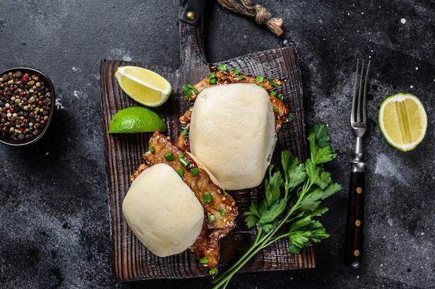 Bun bao gotowane na parze z boczkiem wieprzowym i warzywami. czarne tło. widok z góry.
