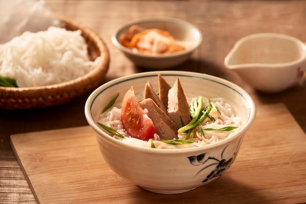 Bun cha ca - jeden z najpopularniejszych makaronów do zup w okolicy nadmorskiej z makaronem ryżowym, grillowaną rybą, zieloną cebulką, pomidorem i sosem rybnym...