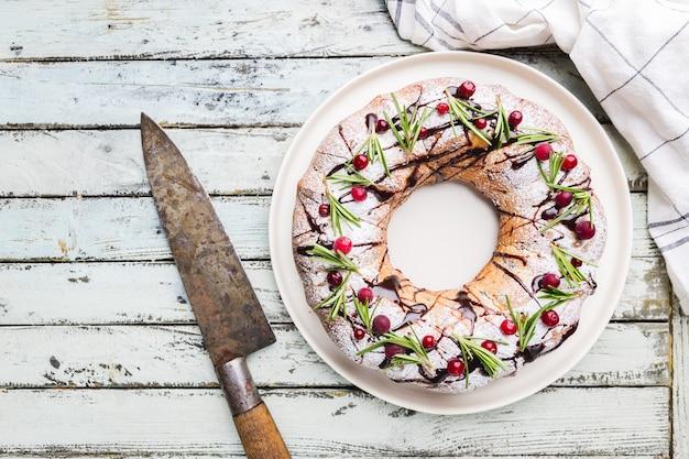 Bundt z żurawiną z czekoladą i pomarańczą na białym talerzu. domowy jesienno-zimowy przytulny deser wakacyjny na rustykalnym drewnianym stole, widok z góry