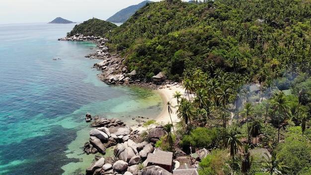 Bungalow i zielona palma kokosowa na tropikalnej plaży. domek na piaszczystym brzegu paradise island z widokiem na drona