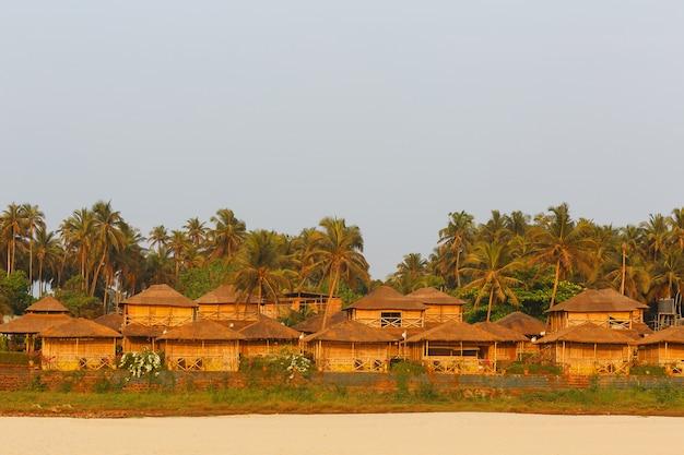 Bungalow na wybrzeżu morza, sieć domów z trzciny bambusowej i liści palmowych. przytulna plaża, goa, indie.