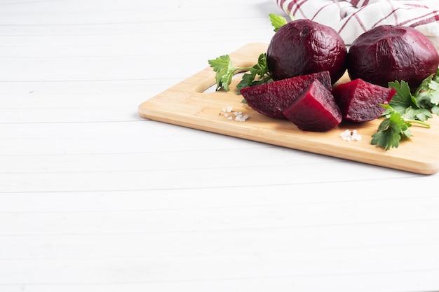 Buraczki gotowane w całości pokrojone na desce do krojenia z liśćmi pietruszki na białym stole. kopiuj przestrzeń,