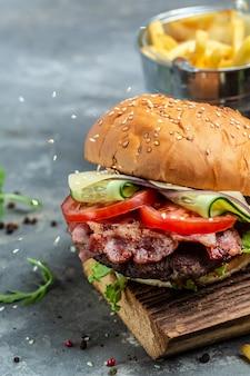 Burger bekonowy z kotletem wołowym. amerykańskie fast foody. patty burger z frytkami i dipami. obraz pionowy. miejsce na tekst.