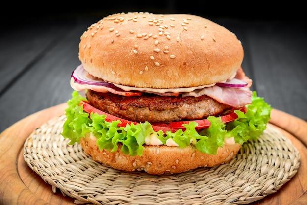 Burger bekonowy z kotletem wołowym z świeżymi warzywami na podłoże drewniane