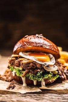 Burger faszerowany rozdrobnionymi pieczarkami z jajek indyczych i frytkami.
