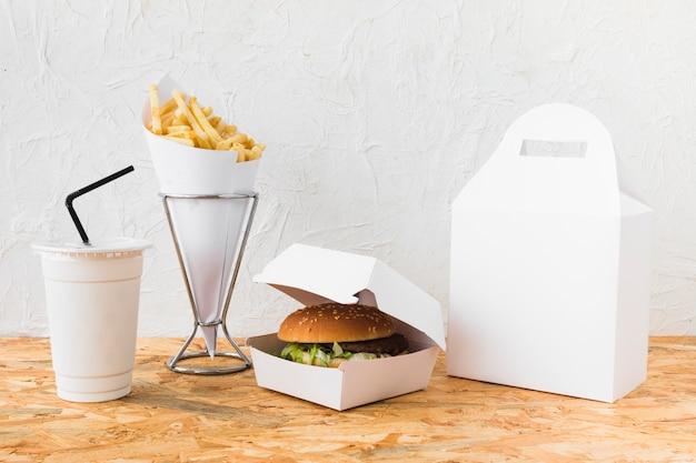Burger; frytki i filiżanka do usuwania na drewnianym stole