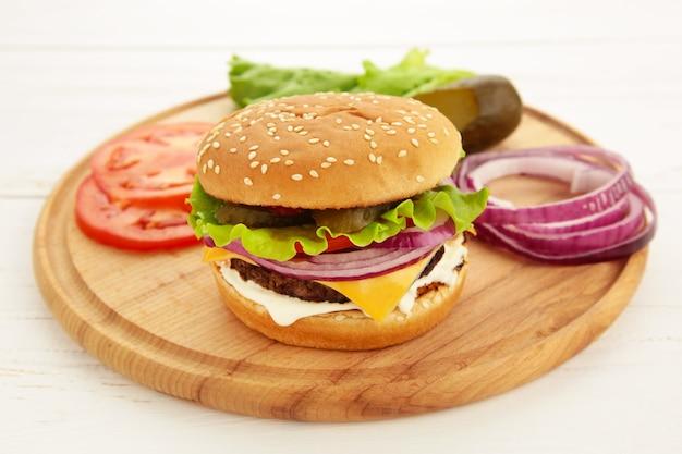 Burger kotlety stek z przyprawami, serem, pomidorami, sałatką i bułką na białym tle. widok z góry