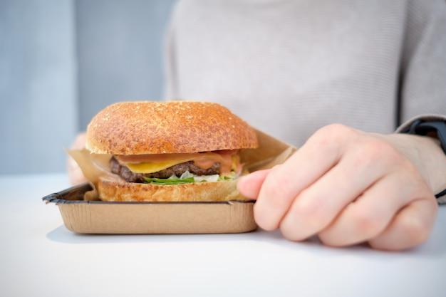 Burger liże stół przed dziewczyną.