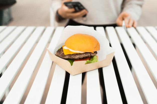 Burger na białym stole na zewnątrz. uliczne jedzenie na wynos w kawiarni. kotlet, ser, warzywa i sos w bułkach. selektywne skupienie