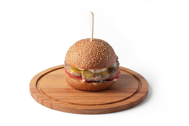 Burger na drewnianej desce na białej powierzchni do dostawy