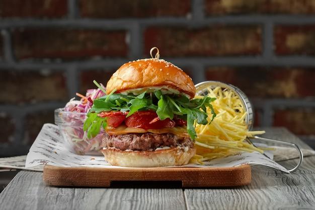 Burger na drewnianym stole z serem, boczkiem, pomidorami, zieloną i czerwoną sałatką oraz frytkami